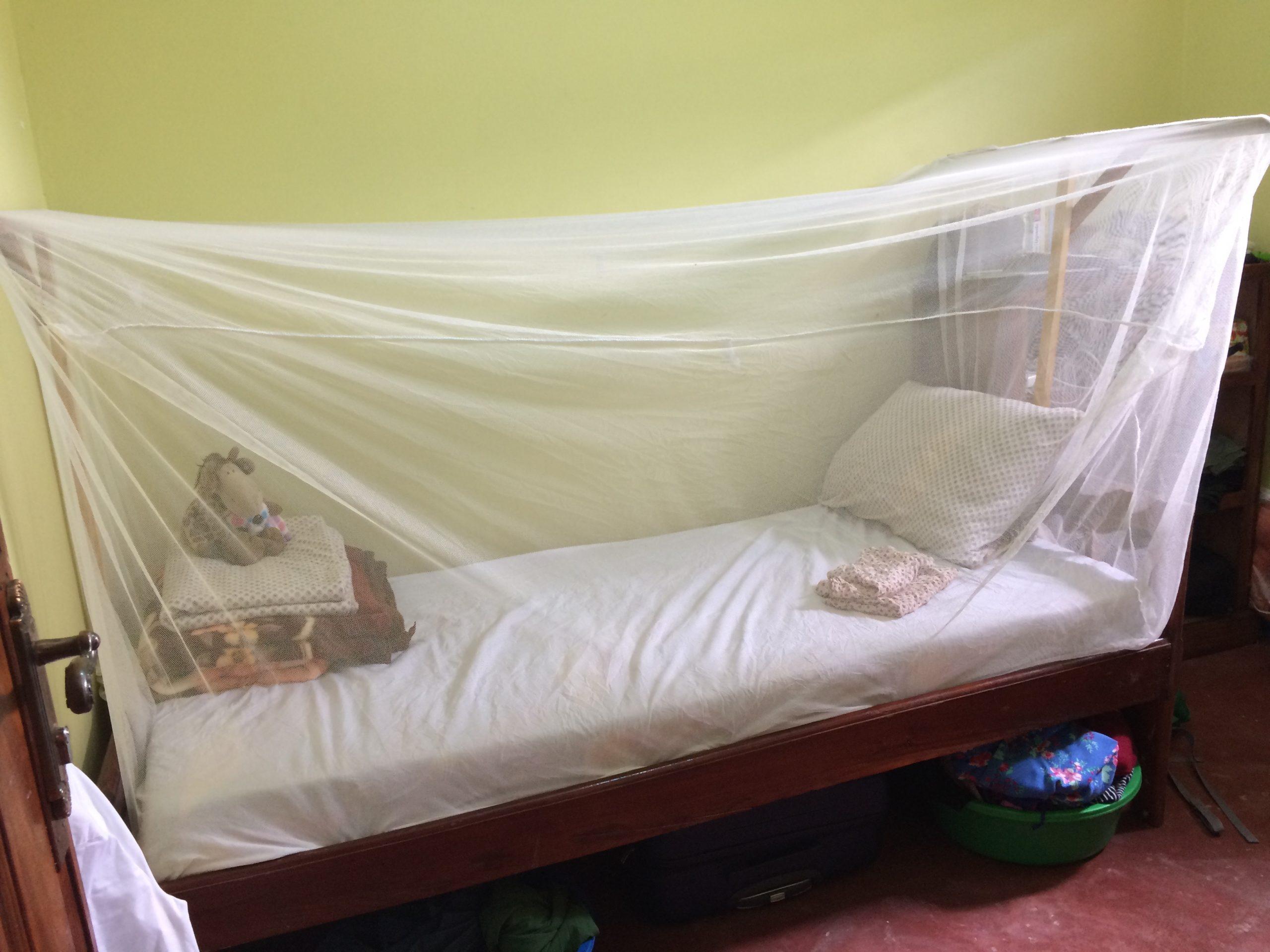 Einfaches, schmales Bett in einem kleinen Zimmer. Braun rote Fußboden, gelb grüne Wand. Auf dem Bet ist das Bettzeug zusammengefaltet und eine Plüschgiraffe zu sehen. Über dem Bett ist ein Moskitonetz gespannt.