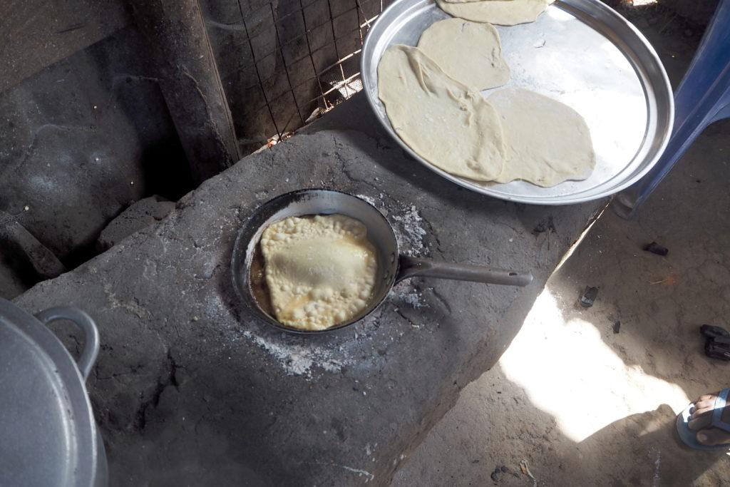 Lehmküche. Auf einer Kochstelle ist eine Pfanne mit Capati (Teigfladen) der Blasen wirft. Daneben das große Tablett mit weiteren ausgerollten, noch rohen Capati Teigfladen.