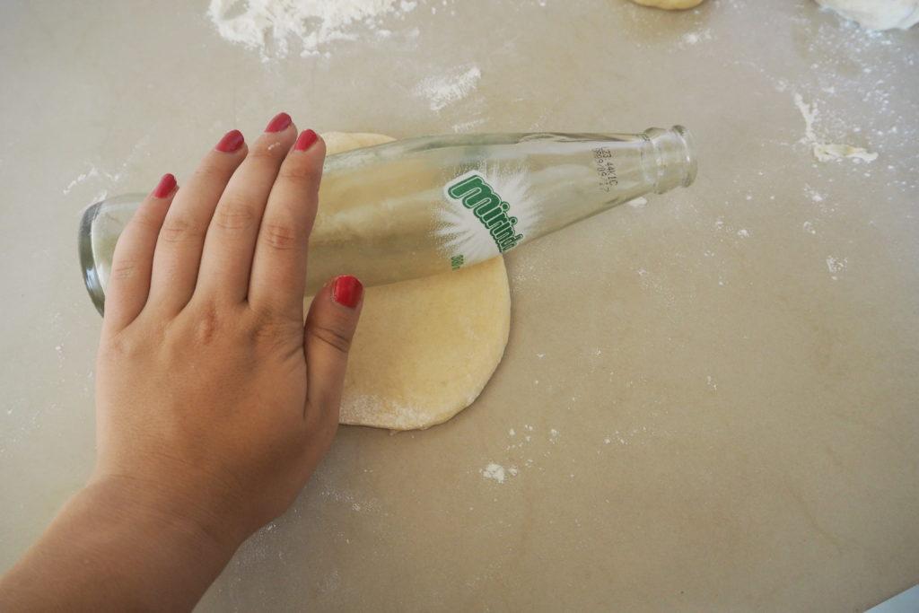 Arbeitsplatte. Auf der Platte sind Mehlspuren zu sehen. Mittig auf der Platte ein kleiner, etwas dicker Teigfladen, dadrauf eine Soda Glasflache die von einer Hand gehalten wird. Glasflasche wird als Nudelholz Ersatz verwendet.